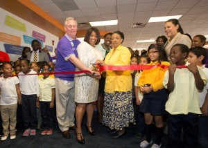 (From L-R) Ted Williams, sales director, FedEx Services; Dr. Shuanta Broadway, principal, Emma Hutchinson Elementary School; and Shirley Miller, media specialist, Hutchinson Elementary cut the ribbon inside the school's new Heart of America/FedEx Cares READesign Reading Corner as Atlanta Board of Education (District 6) Member Eshé P. Collins (far center) and Atlanta Public Schools Superintendent Meria J. Carstarphen (far right) look on.